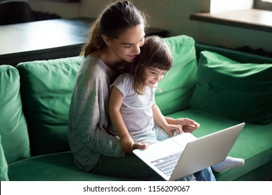 Happy mother with little kid daughter having fun online with application, watching video cartoons or playing game on laptop together, young babysitter or nanny teaching child girl to use computer