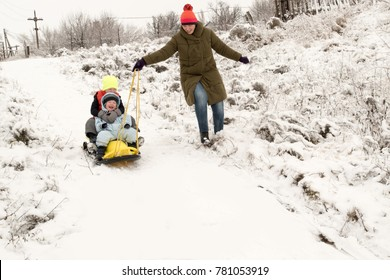 A happy mother with little kids in colorful clothes posing in front of a photographer with a new yellow sled. Picturesque area with a bridge on the river. The concept of winter vacations, Christmas