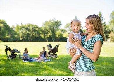 Happy mother looking at cute daughter with friends and children in background at park