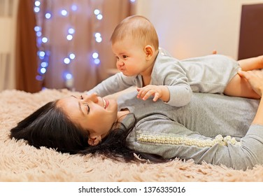 Happy mother lying on the bed and playing with her baby.