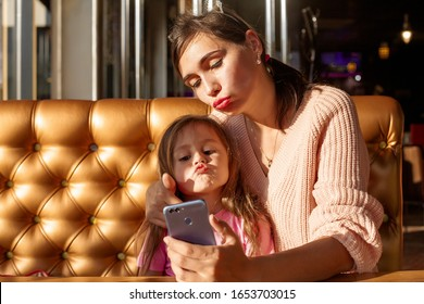 Happy mother make selfie with her smartphone in cafe