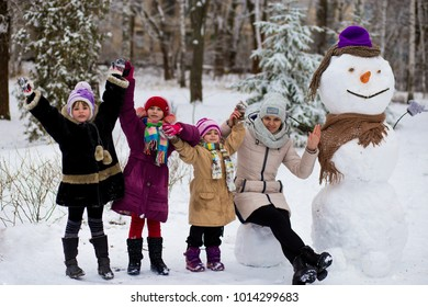 Happy mother of many children sculpt a big real snowman, Big Happy family have fun in a winter park
