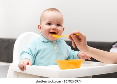 Happy Mother Nanny Or Sister Feeds A Little Baby With A Spoonful Of Food At Home