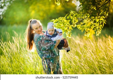 Happy mother with the newborn son walk in the park, gently embrace and smile