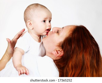 A happy mother playing with a baby
