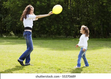 Happy mother playing with her daughter in the park with balloon