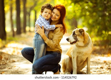 happy mother playing with her son in the park and dog sitting and watching