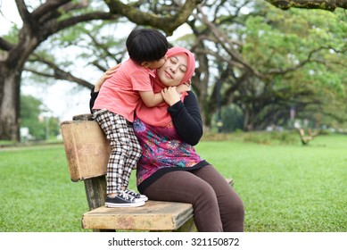 Happy mother playing with her son in the park.