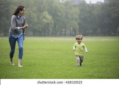 Happy Mother playing with her toddler son outdoors. Love and togetherness concept.