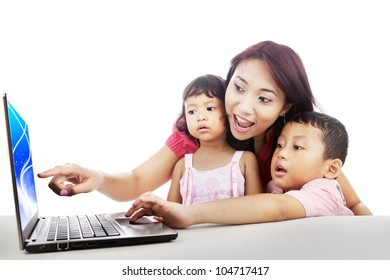 Happy mother pointing on the screen of laptop with her children surfing on internet