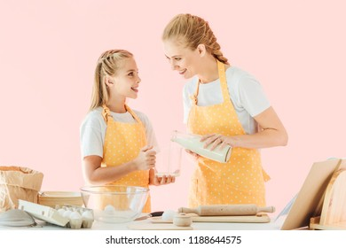 happy mother pouring milk for preparing dough with daughter isolated on pink