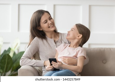 Happy mother and preschool daughter having fun at home, smiling young mum and little child using phone together, laughing at funny video, playing game, mobile apps, embracing, sitting on couch