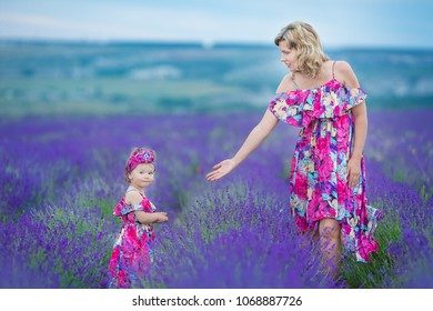 Happy mother with pretty daughter on lavender background. Beautiful woman and cute baby playing in meadow field. Family holiday in summer day