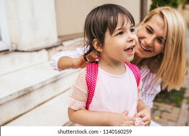 Happy mother and pupil daughter preparing backpack to going to preschool sitting on the stairs of the home outdoor. Good relationship. Cute little girl with her mom feel happy before the preschool day