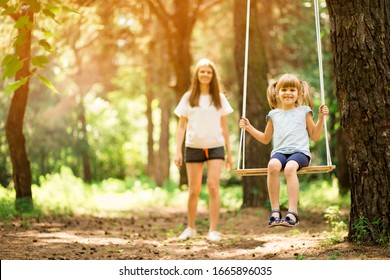 happy mother pushing laughing daughter on swing in summer park. Happy childhood without internet and electronic gadgets