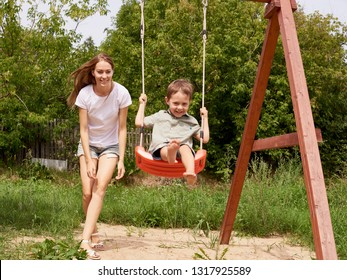 happy mother pushing laughing son on swing in a park