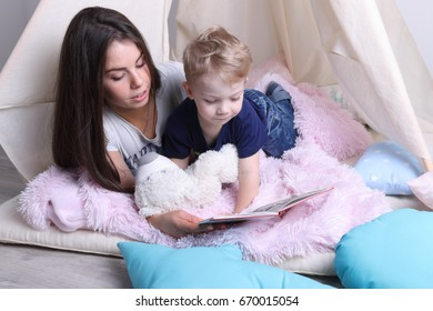 Happy mother reads book for her little cute son among pillows