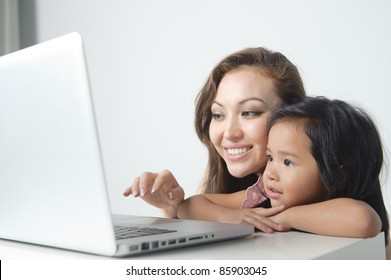 Happy Mother showing daughter how to use a computer