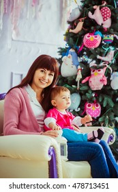 Happy mother sits with her daughter on soft beige chair before Christmas tree