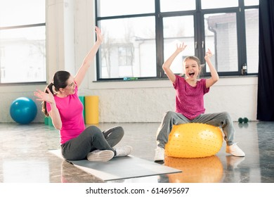Happy mother sitting on yoga mat and daughter on fitness ball having fun in gym