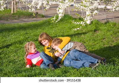 Happy mother with small children in spring recreation ground