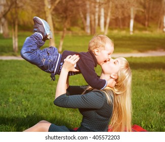 Happy mother with small son play on the lawn in the park in spring sunny day