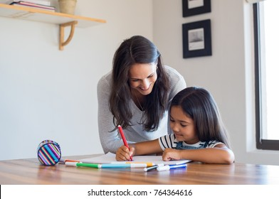 Happy mother and smiling daughter together painting using markers. Mother helping adopted child with art homework. Cheerful mother and asian little girl making painting at home.
