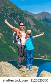 happy mother and son with backpacks high in the mountains against the backdrop of Lake Morskie Oko, Poland