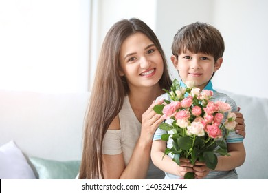 Happy mother and son with bouquet of flowers at home