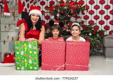 Happy mother with son and daughter in front of Christmas tree having fun with presents