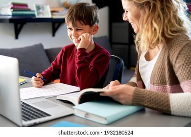 Fröhliche Mutter und Sohn, die zusammen Hausaufgaben machen