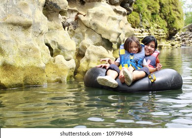 Happy mother and son floating on inflatable tube in river during vacation