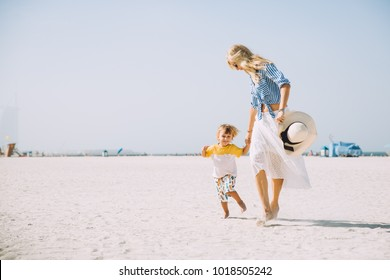 Happy mother and son having fun on the beach