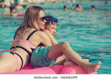 Happy mother and son having fun on inflatable floater in swimming pool on summer vacation.