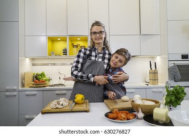 Happy mother and son hugging in the kitchen. Family preparing dinner together.
