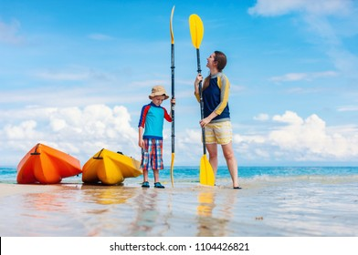 Happy mother and son with kayaks at tropical beach