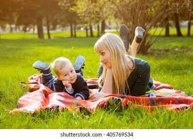 happy mother and son lie on the rug and having fun on the grass in the park in spring sunny day