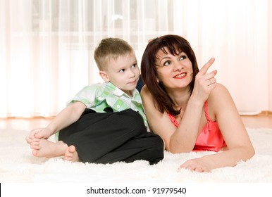 happy mother and son lie on the carpet