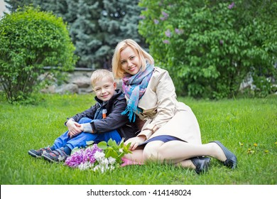Happy mother and son in park sitting on green grass in spring
