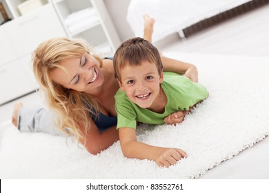 Happy mother and son playing in the living room wrestling on the floor