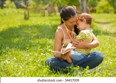 Happy mother and son reading a book outdoors