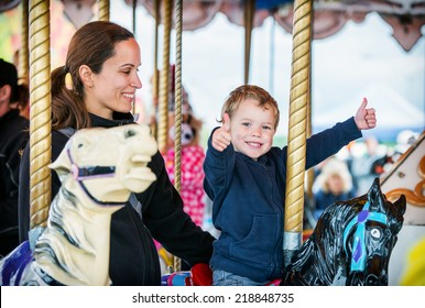 A happy mother and son are riding on a merry-go-round carousel together, smiling and having fun at a fair or amusement park.  The boy holds two thumbs up.