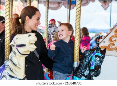 A happy mother and son are riding on a merry-go-round carousel together sharing a moment, smiling at one another having fun at a fair or amusement park.  The boy holds a thumbs up at the mother.