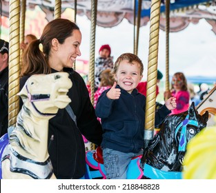 A happy mother and son are riding on a merry-go-round carousel together, smiling and having fun at a fair or amusement park.  The boy holds a thumbs up.