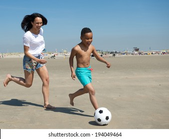 Happy mother and son running on beach with ball in summer