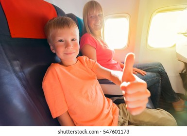 """Happy mother and son sitting in airplane and small boy showing """"good"""".  Focus on the face of boy."""