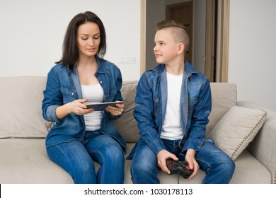 Happy mother and son sitting on sofa and playing console at home