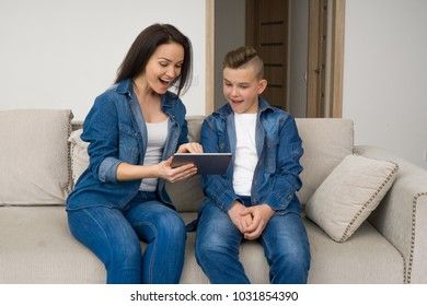 Happy mother and son sitting on sofa and using digital tablet at home