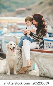 Happy mother and son sitting on the quay with dog. happy mother playing with her son near the sea playing with the dog