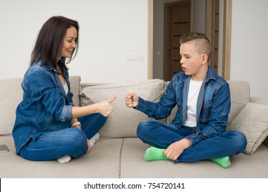 Happy mother and son sitting on sofa and playing rock paper scissors at home